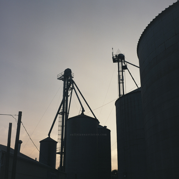 grain silos at sunset silhouettes